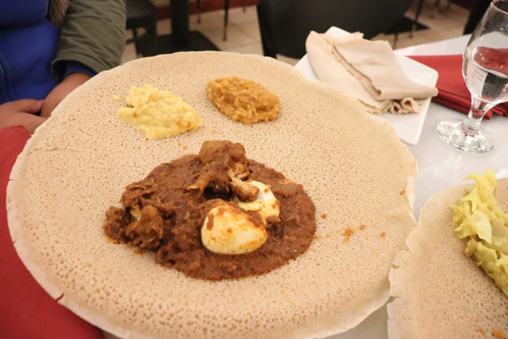 Doro Wot, spiced chicken with hard-boiled eggs served over injera (Ethiopian style flatbread).