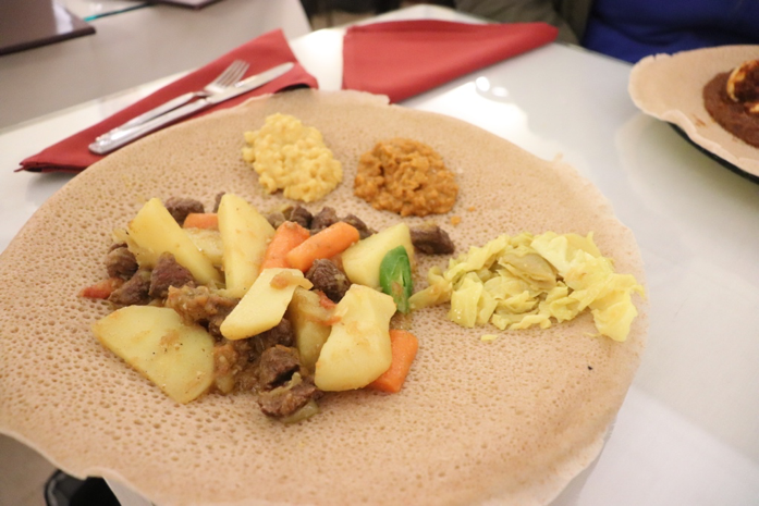 Yesega Alicha Be Dnish, seasoned beef, carrots, and potatoes served with mashed lentils and steamed cabbage over injera (Ethiopian style flatbread).